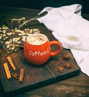 Roter keramischer becher mit kaffee auf braunem hölzernem