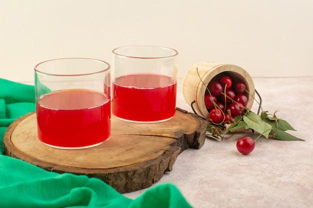 Roter kirschsaft der vorderansicht mit frischen kirschen auf dem fruchtcocktailgetränk der rosa schreibtischfarbe