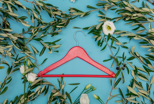 Roter kleiderbügel mit olivenzweigen auf blauem hintergrund. ansicht von oben