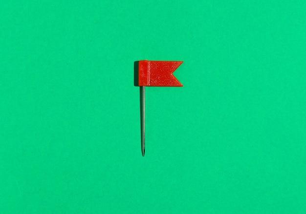 Roter kleiner flaggenstift auf grünem hintergrund. sicht von oben .