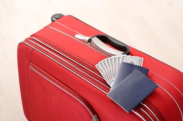 Roter koffer, pässe und geld auf einem holzboden in leerem raum