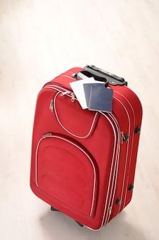 Roter koffer und pässe auf einem holzboden im leeren raum