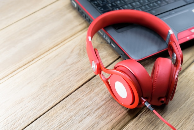 Roter kopfhörer gesetzt auf den schwarzen laptop oder das notizbuch und auf den holztisch
