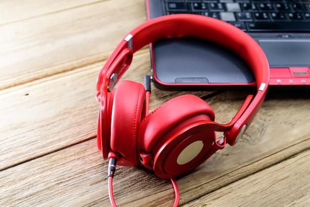 Roter kopfhörer platziert auf den schwarzen laptop oder das notizbuch