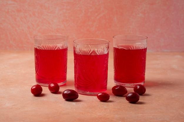 Roter kornelkornsaft in gläsern.