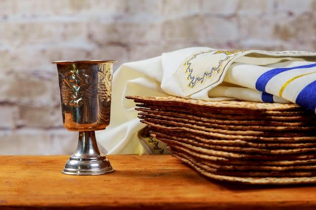 Roter koscherer wein mit einem weißen teller matzah oder matza und einer passah-haggada