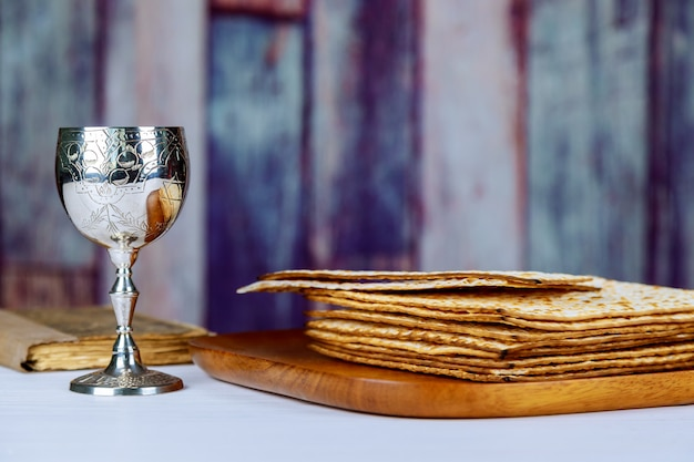 Roter koscherer wein mit einem weißen teller matzah oder matzo und passahfest haggadah
