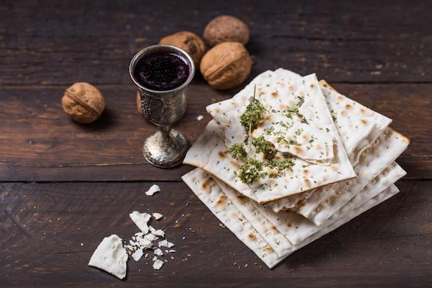 Roter koscherer wein mit einer weißen matzah oder matza auf einer vintage holzwand, die als pessach-seder-mahlzeit mit kopierraum präsentiert wird.