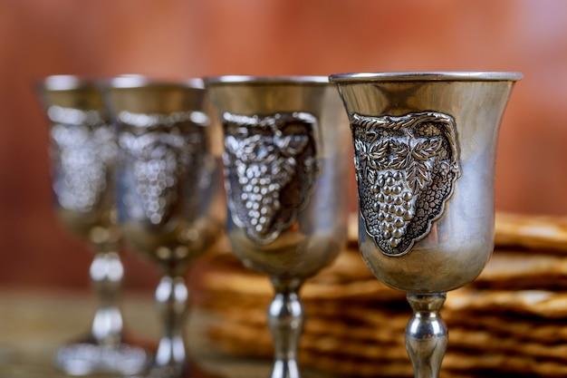Roter koscherer wein vier von matzah oder von matza passahfest haggadah auf einem hölzernen hintergrund der weinlese