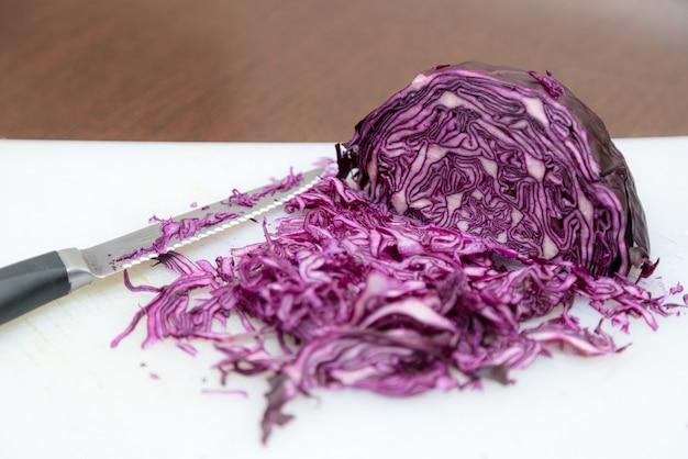 Roter krautsalat auf schneidebrett mit küchenmesser an der seite gehackt.