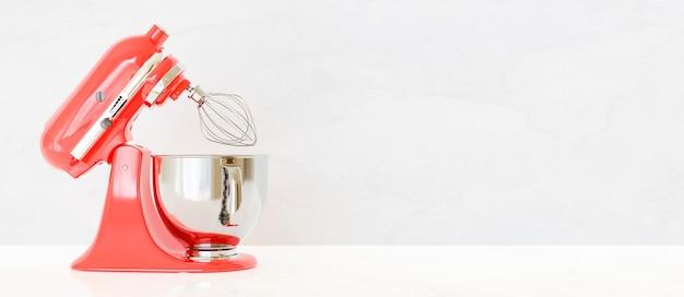 Roter küchenmixer seitlich auf weißer oberfläche