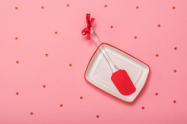 Roter küchenspatel in einer weißen schüssel auf rotem grund mit sternen. küchengeräte auf festlichem hintergrund. flach liegen.