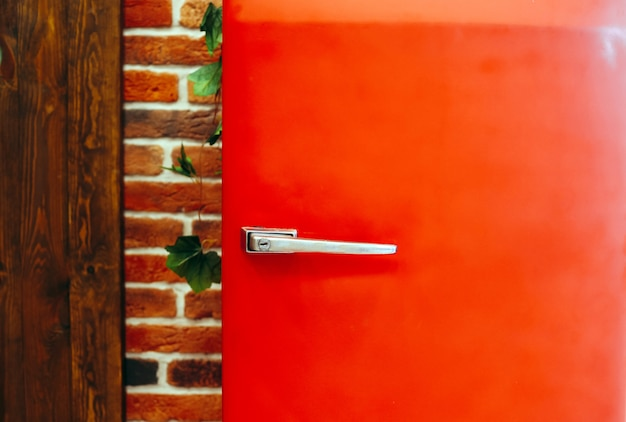 Roter kühlschrank der retro- weinleseart gegen backsteinmauer