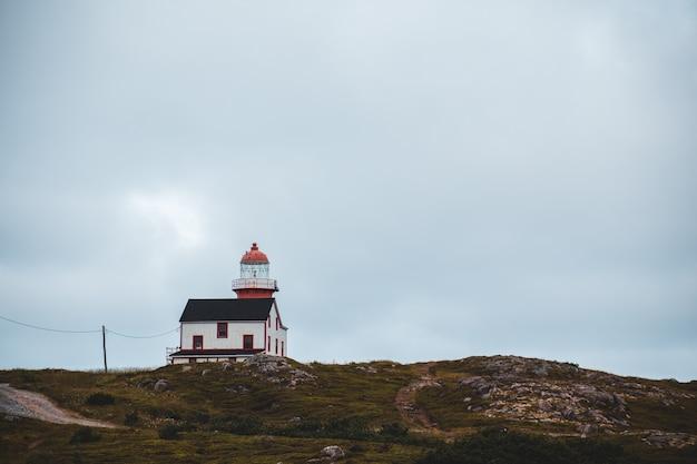 Roter leuchtturm auf dem hügel