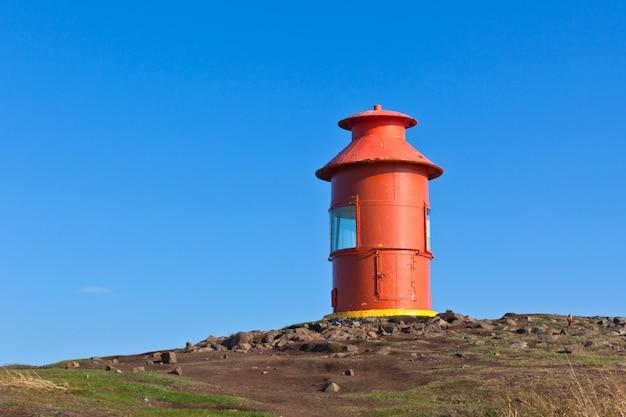 Roter leuchtturm auf einem hügel, island