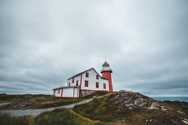 Roter leuchtturm neben weißem haus