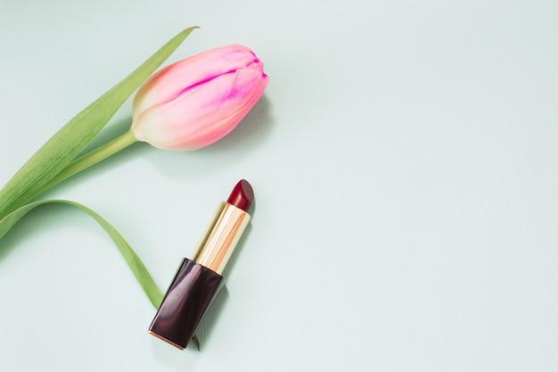 Roter lippenstift auf einem weichen blauen pastellhintergrund. tulpenblume und lippenstift. platz für text. internationaler frauentag