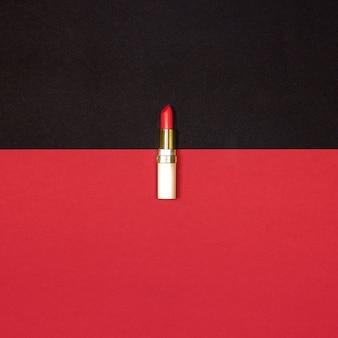 Roter lippenstift auf schwarzem und rotem hintergrund - ansicht von oben