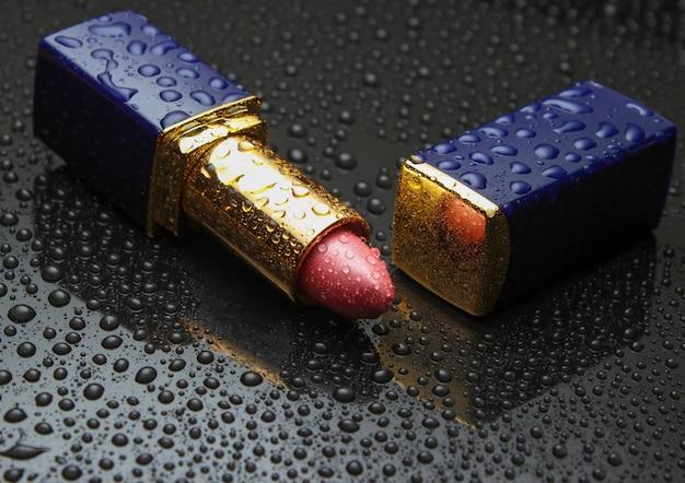 Roter lippenstift mit wassertropfen auf dunklem schwarz. schönheit und mode.