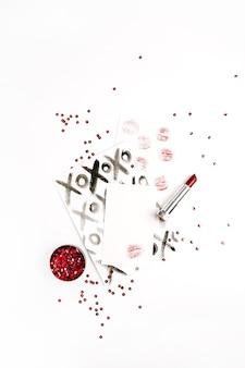 Roter lippenstift, weibliche kussform und konfetti. flache lage, ansicht von oben.