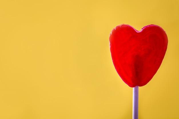 Roter lutscher mit herzform auf gelber oberfläche lieben sie konzept. valentinstag.