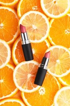 Roter mattlippenstift auf einem hintergrund von orangen und zitronen. draufsicht auf kosmetisches konzept auf zitrushintergrund. damenaccessoires, sommer-make-up-konzept flach.