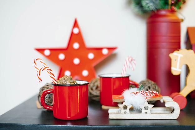 Roter metallbecher mit kakao und zuckerstange mit weihnachtsdekor