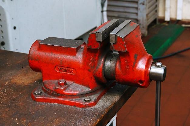 Roter metallschraubstock auf holztisch in der fabrik