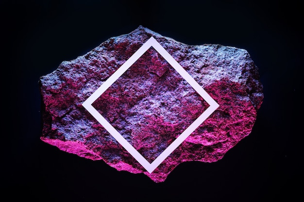 Roter meteorit im dunklen raum mit weißem rahmen und neonbeleuchtung im kopierraum.
