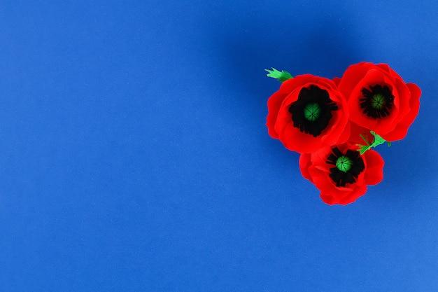 Roter mohn anzac-papiertag, erinnerung, erinnern sich, memorial day-krepppapier auf blauem hintergrund.