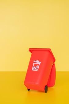 Roter müllbehälter auf gelbem hintergrund