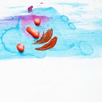 Roter nagellacktropfen und -anschlag auf befleckter blauer beschaffenheit über weißem hintergrund