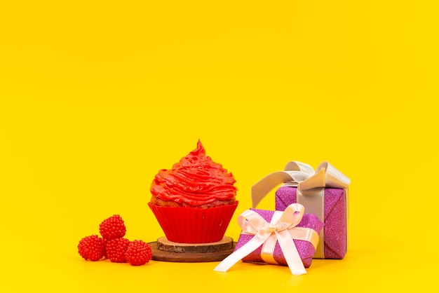 Roter obstkuchen der vorderansicht mit frischen roten himbeeren und lila geschenkboxen auf gelbem schreibtisch