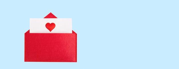 Roter offener umschlag des banners mit einem blatt papier mit einem herzen auf einem blauen hintergrund mit copyspace. valentinstag feiertagskonzept und liebesnotizen