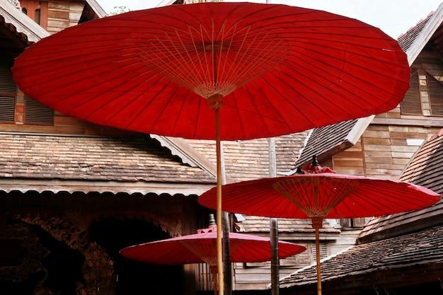 Roter papierregenschirm und hölzernes haus