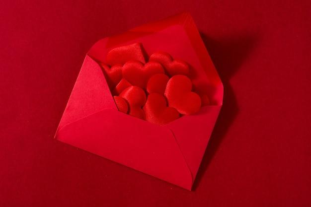 Roter papierumschlag mit dem herzinnere lokalisiert auf rotem oberflächenvalentinstagkonzept.