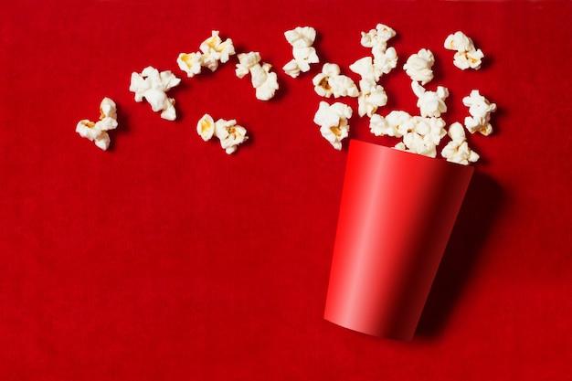 Roter pappbecher mit verstreutem popcorn auf rot