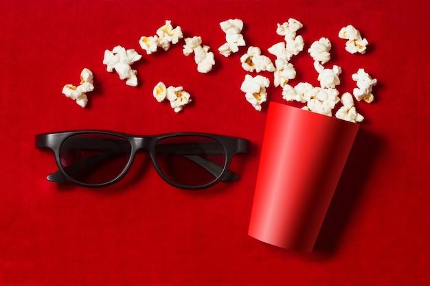 Roter pappbecher mit verstreutem popcorn und gläsern auf rot