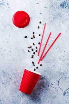 Roter pappbecher mit verstreuten kaffeebohnen und röhrchen auf grauer alter betonoberfläche. draufsicht mit kopienraum.