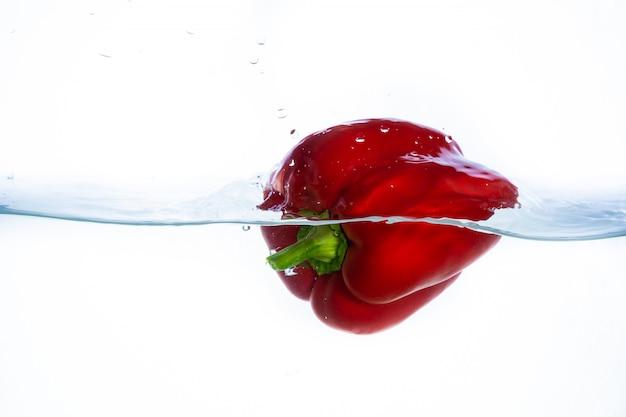 Roter paprika fällt ins wasser und erzeugt schöne luftblasen und wasserspritzer