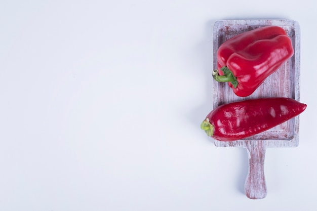 Roter paprika und paprika auf einem holzbrett, draufsicht.