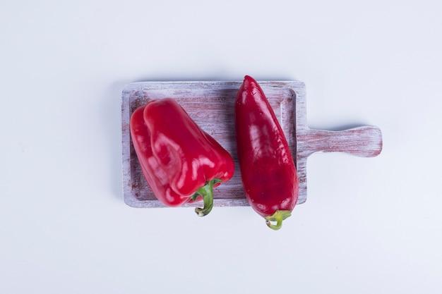 Roter paprika und paprika auf einem holzbrett in der mitte