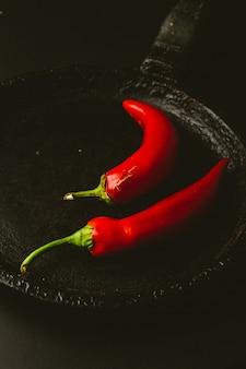 Roter paprikapfeffer auf schwarzem