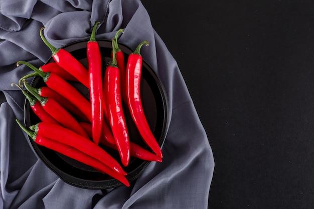 Roter pfeffer in der schwarzen schüssel auf stoff auf schwarzer oberfläche
