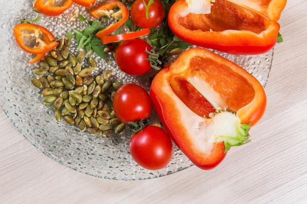Roter pfeffer mit tomatenkirsche und -samen in hellem holztisch der glasplatte n. zutaten in der platte