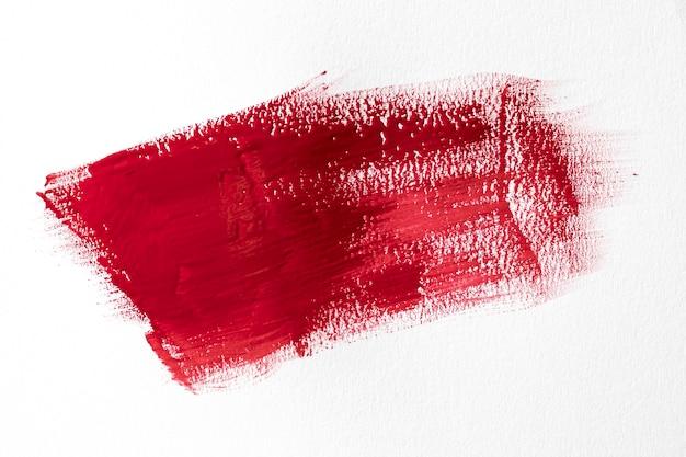 Roter pinselstrich auf weißem hintergrund