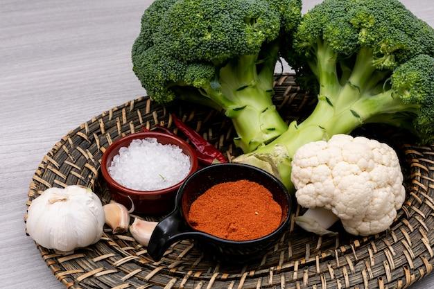 Roter pulverpfeffer und -salz des frischen brokkoliknoblauch-blumenkohls