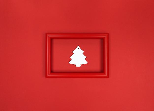 Roter rahmen, mit weißem hölzernen weihnachtsbaumspielzeug innen.
