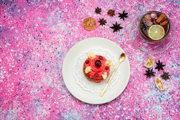 Roter rahmkuchen der draufsicht mit heißem tee auf der süßen zuckerfarbe des farbigen hintergrundkuchenkekses
