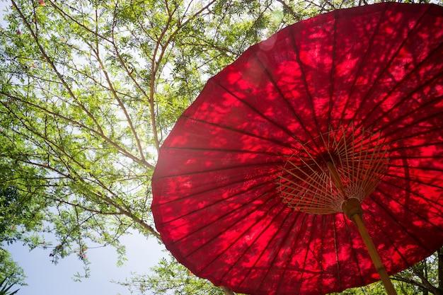 Roter regenschirm im garten-erholungsort